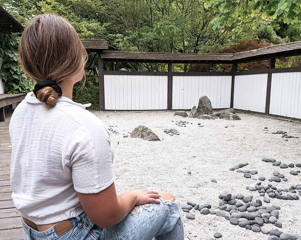 rachel hannah sitting inside of michigan state univesities zen garden in east lansing, michigan